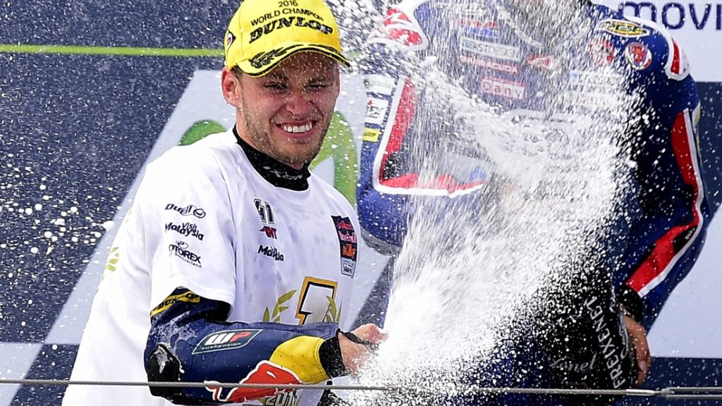 New Moto 3 World champion, Red Bull KTM Ajo's South African rider Brad Binder, celebrates on the podium after the Moto 3 race of the Aragon Grand Prix at the Motorland racetrack in Alcaniz on September 25, 2016. / AFP PHOTO / JOSE JORDAN