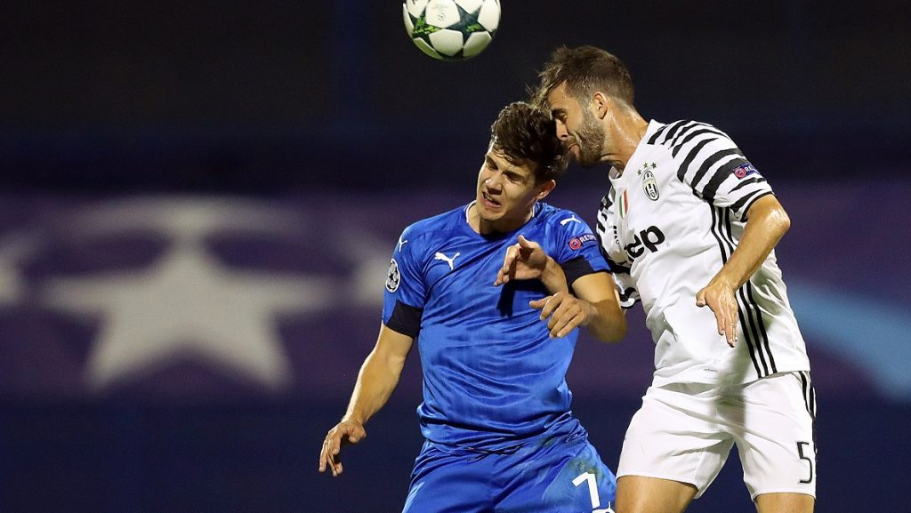 Dinamo Zagreb's Croatian midfielder Mario Situm (L) heads the ball with Juventus' Bosnian midfielder Miralem Pjanic during the UEFA Champions League group H football match between Dinamo Zagreb and Juventus Turin at the Maksimir Stadium in Zagreb on September 27, 2016. / AFP PHOTO / STR