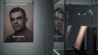 """A rare manuscript (R) belonging to British mathematician and code breaker Alan Turing (L, depicted on a poster) is displayed in Hong Kong on March 19, 2015. The handwritten notebook from the early 1940s gives an intimate insight into the """"father of the modern computer"""" and was shown ahead of an auction in New York where it is expected to fetch at least one million USD.  AFP PHOTO / Philippe Lopez / AFP PHOTO / PHILIPPE LOPEZ"""
