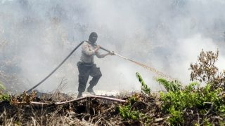 Indonesian police extinguisher spray water a fire on burning peatland forest on the Rimbo Panjang village, Kampar district of riau province, indonesia;September, 1, 2016. Indonesia's forest fires will happen again.Forest and plantation fires on Indonesia's Sumatra island at the onset of the dry season (Photo by Afrianto Silalahi/NurPhoto)