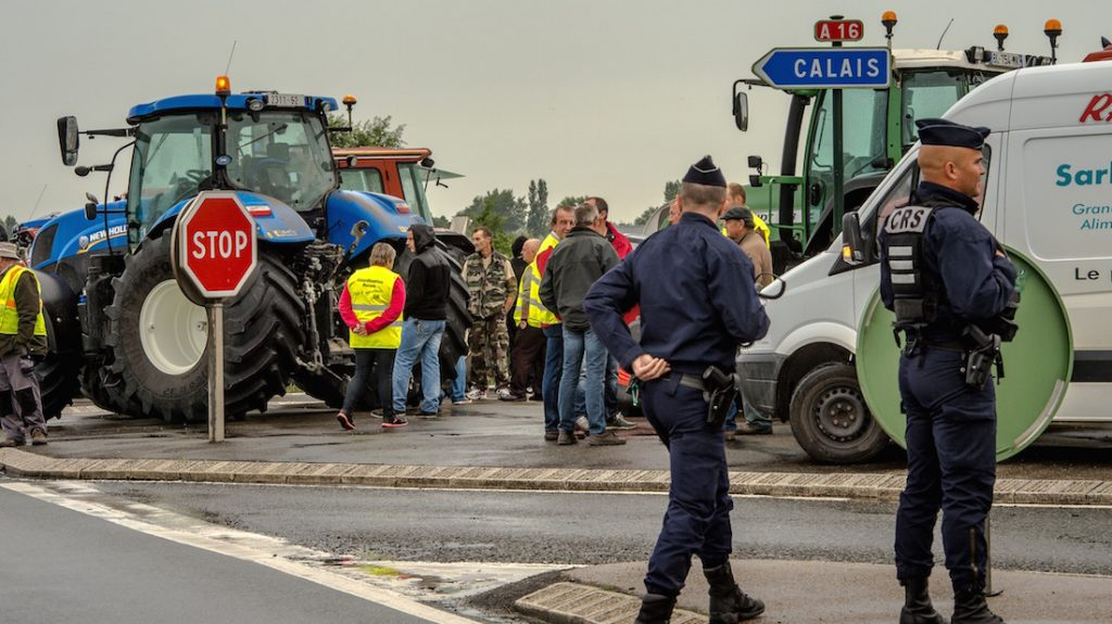 "French police officers stand guard as French farmers gather at Marck on September 5, 2016, prior to a ""go-slow"" protest with truck drivers on the A16 highway calling for the dismantling of the so-called ""Jungle"" migrant camp in the French northern port city of Calais. French farmers and truckers launched a joint operation on Septenber 5, 2016 to block off main routes in and out of Calais to call for the closure of the sprawling ""Jungle"" migrant camp there. Around 70 trucks began a ""go-slow"" on the main A16 motorway -- the main artery for freight and passengers heading for Britain either via the Channel Tunnel or the Calais port. / AFP PHOTO / PHILIPPE HUGUEN"