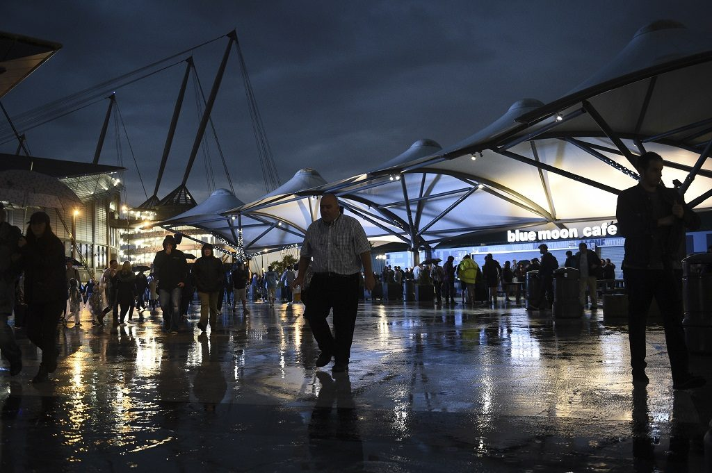 Fans leave the Etihad stadium in Manchester, northwest England, on September 13, 2016 after the UEFA Champions League group C football match between Manchester City and Borussia Monchengladbach was postponed due to heavy rain. / AFP PHOTO / OLI SCARFF
