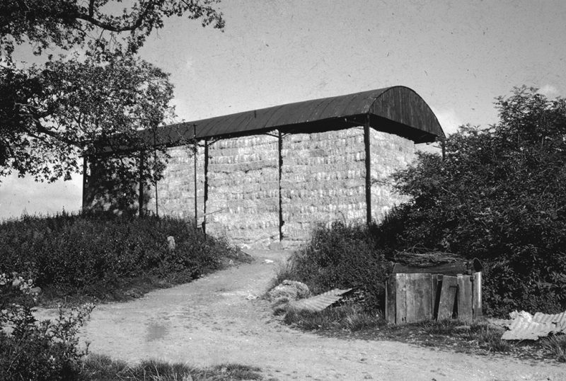 A photograph of a covered building with no sides used to store bales of hay, the bales are stacked several stories high, the building is situated on a dirt road surrounded by grass and bushes, discarded trash can be seen in the foreground, 1961. (Photo by Smith Collection/Gado/Getty Images).