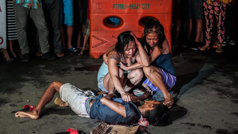 MANILA, PHILIPPINES - JULY 23: (EDITORS NOTE: Image contains graphic content.)  Two women cry in grief after armed assailants in a motorcycle shot their loved one in a main thoroughfare on July 23, 2016 in Manila, Philippines. The victim was an alleged drug peddler a claim disputed by his wife and maintained her husband is nothing more than a pedicab driver plying his trade when he was shot in front of her. Philippine President Rodrigo Duterte declared a war on crime and drugs after winning the presidential elections on May 9, 2016. President Duterte has recently been living up to his nickname, 'The Punisher', as Philippine police have been conducting night time drug raids on almost a daily basis. With reports of at least 300 drug related deaths since the start of July, Human rights groups and the Catholic church have objected to the use of brutal force by the Police. (Photo by Dondi Tawatao/Getty Images)