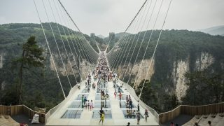 Visitors cross the world's highest and longest glass-bottomed bridge above a valley in Zhangjiajie in China's Hunan Province on August 21, 2016. / AFP PHOTO / FRED DUFOUR