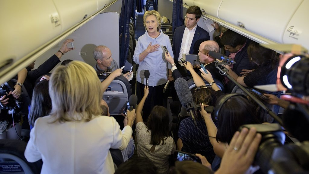 Democratic presidential nominee Hillary Clinton speaks to the press onboard her plane September 5, 2016 above Iowa. / AFP PHOTO / Brendan Smialowski