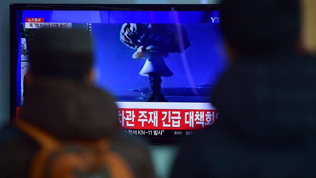 """ADDITION-People watch a news report on North Korea's first hydrogen bomb test at a railroad station in Seoul on January 6, 2016. South Korea """"strongly"""" condemned North Korea's shock hydrogen bomb test and vowed to take """"all necessary measures"""" to penalise its nuclear-armed neighbour.  The image shown on TV shows files images from other nuclear tests from other countries and the caption in red at the bottom of the screen reads """"the Blue House will convene an emergency meeting of the NSC, the National Security Council.""""   AFP PHOTO / JUNG YEON-JE / AFP PHOTO / JUNG YEON-JE"""