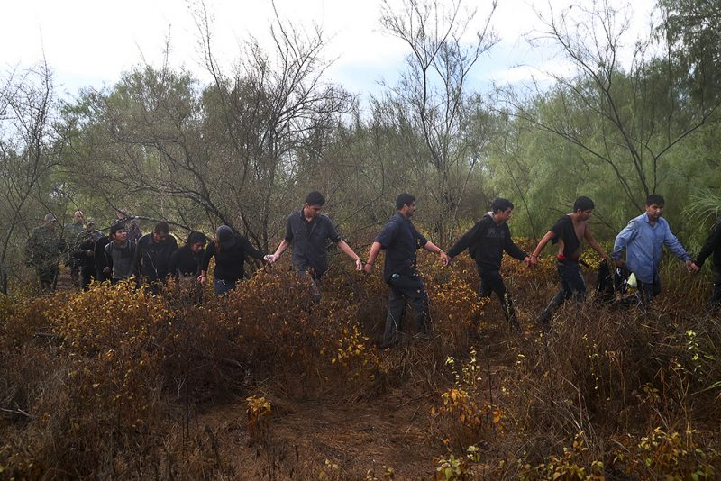 ROMA, TX - AUGUST 16:  Detained  immigrants are led through the brush after being captured by U.S. Border Patrol agents on August 16, 2016 in Roma, Texas. Border security has become a main issue in the U.S. Presidential campaign, as Republican Presidential candidate Donald Trump has promised to build a wall, at Mexico's expense to fortify the U.S.-Mexico border.  (Photo by John Moore/Getty Images)
