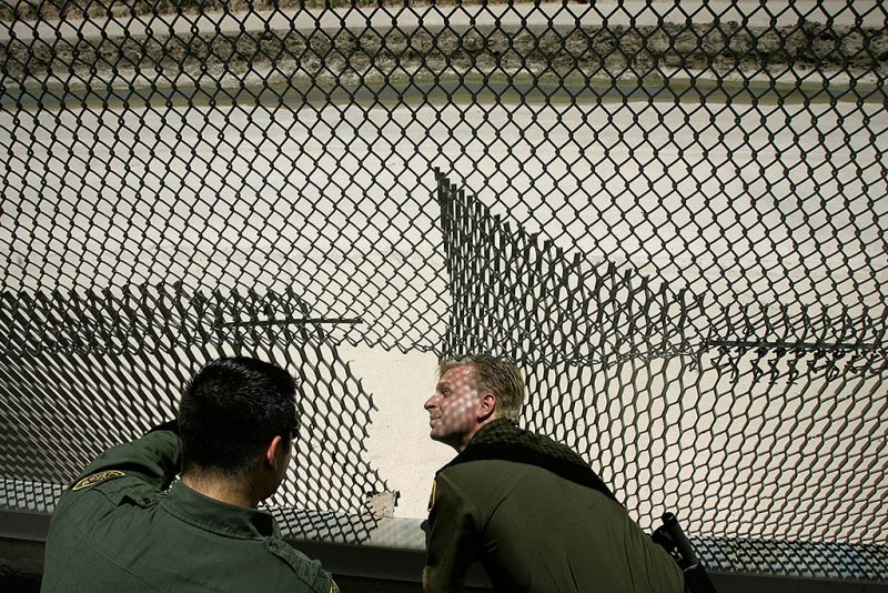 """EL PASO, TX - JUNE 26:  U.S. Border Patrol Agent Patrick Berry (R) inspects a hole that had just been cut in the fence along the US-Mexico border June 26, 2007 in El Paso, Texas. The Border Patrol is nearly constantly repairing holes cut and torn in the fences separating the US and Mexico. According to Majority Leader Harry Reid (D-NV), the Senate took a step closer to passing comprehensive immigration legislation today that could possibly grant 12 million people living in the United States """"a pathway to legalization.""""  (Photo by Chip Somodevilla/Getty Images)"""