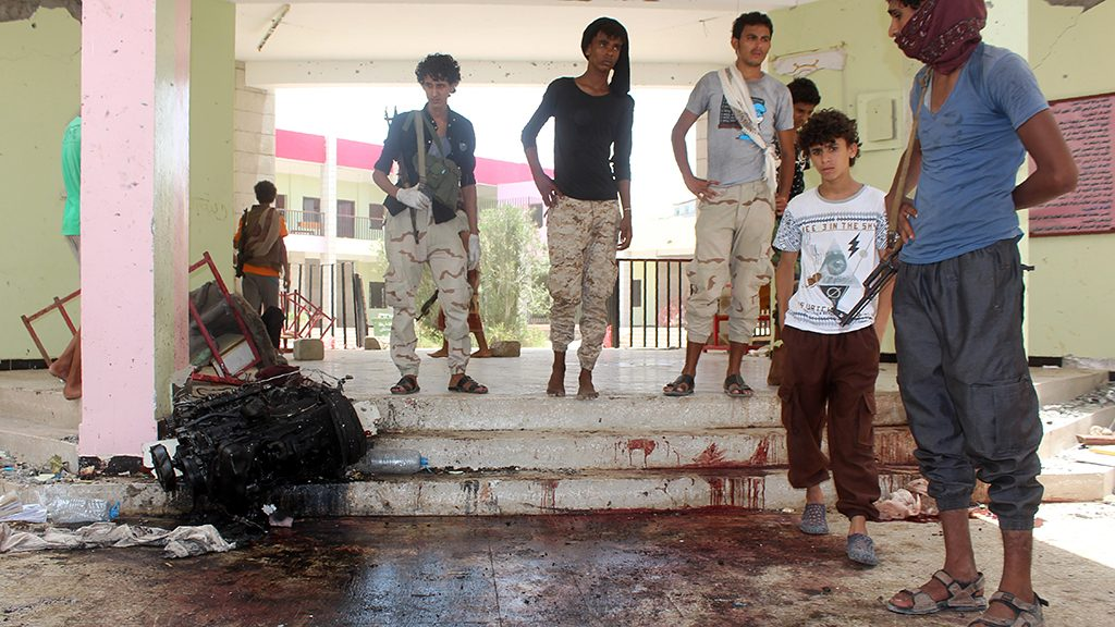 Yemenis look at a blood stained floor at an army recruitment centre following a suicide car bombing claimed by the Islamic State group on August 29, 2016 in the southern Yemeni city of Aden.