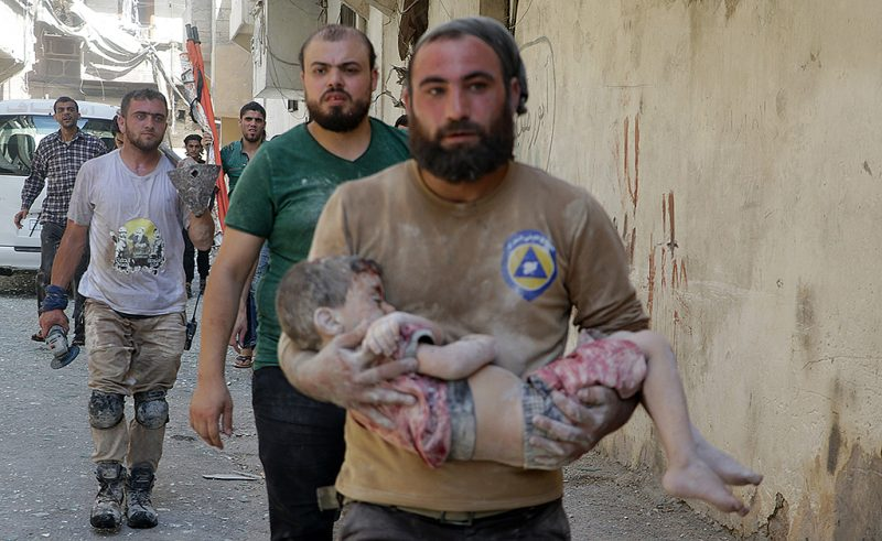 ALEPPO, SYRIA - JULY 17: (EDITOR'S NOTE: Image contains graphic content.) A Syrian man carries a wounded boy in his arms after the war-craft belonging to the Russian army bombed the opposition controlled residential area at the Al-Maysir neighborhood in Aleppo, Syria on July 17, 2016.  (Photo by Ibrahim Ebu Leys/Anadolu Agency/Getty Images)