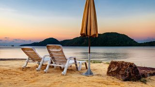 Summer Vacation end concept. Sunset tropical beach with two old chairs and a folded umbrella. Landscape with a quiet sea and the mountain in the distance, Koh Chang, Thailand.