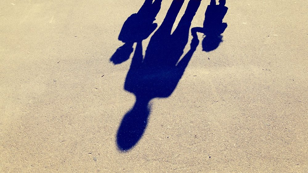 Shadows of mother with son and daughter holding hands on the road