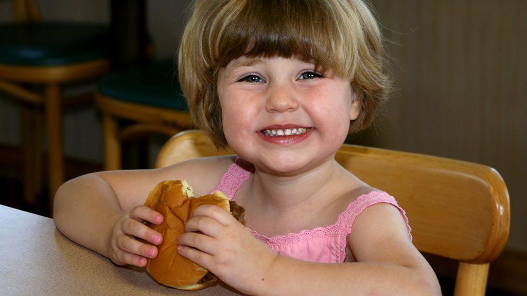 Girl eating hamburger in fast-food restaurant