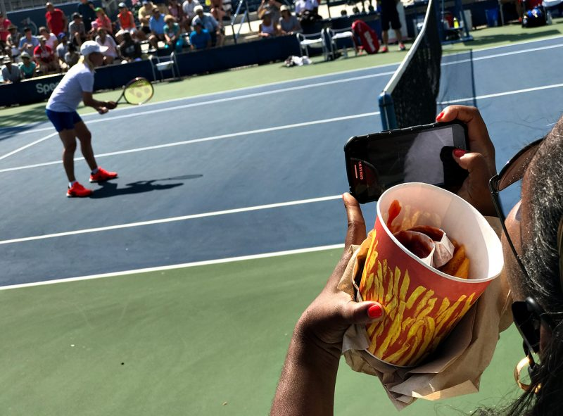 NEW YORK, NY - SEPTEMBER 08:  A spectator snaps a photo of Martina Navratilova while holding a bucket of fries during the women's Championship Doubles Semifinals on a 90+ degree day.  Martina Navratilova and Arantxa Sánchez Vicario defeated Tracy Austin and Gigi Fernandez. Day Eleven of the 2016 US Open at the USTA Billie Jean King National Tennis Center on September 8, 2016 in Queens.  (Landon Nordeman for ESPN)