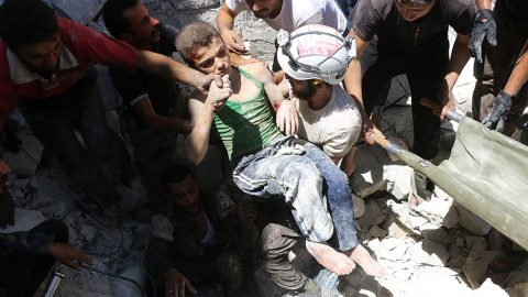 Syrian civil defence volunteers, known as the White Helmets, carry a young boy after they dug him out from under the rubble of buildings destroyed following reported air strikes on the rebel-held neighbourhood of Al-Mashhad in the northern city of Aleppo, on July 25, 2016.Air strikes and barrel bomb attacks killed 16 civilians in rebel-held parts of Aleppo province, with rebel rocket fire onto government areas killing three more, the Britain-based Syrian Observatory for Human Rights said. / AFP PHOTO / THAER MOHAMMED