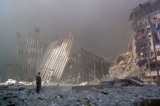 (FILES) This file photo taken on September 11, 2001 shows a man standing in the rubble and calling out asking if anyone needs help after the collapse of the first World Trade Center Tower in New York City. The Twin Towers of the World Trade Center which were struck by hijacked airplanes collapsed on that day claiming 2,753 lives. September 11, 2016 marks the fifteenth anniversary of the event. / AFP PHOTO / DOUG KANTER