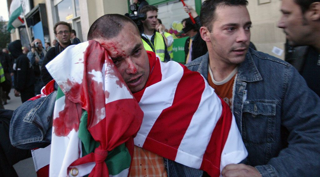 An injured far-right protestor is led to safety during clashes with riot policemen (not pictured) using teargas and water cannons to disperse them 23 October 2006 in central Budapest, as Hungary commemorates the 50th anniversary of the 1956 anti-Soviet uprising amid the worst political divisions in the country since the end of communism. Hungarian police fired rubber bullets and several people were injured in Elizabeth Square, some two kilometres (one mile) from the parliament where official ceremonies were being held to mark the anniversary.    AFP PHOTO / ATTILA KISBENEDEK / AFP PHOTO / ATTILA KISBENEDEK