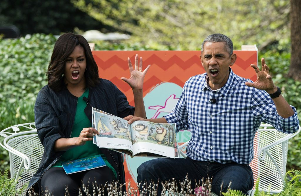 """US President Barack Obama and First Lady Michelle Obama read Maurice Sendak's """"Where the Wild Things Are"""" to children at the annual Easter Egg Roll at the White House in Washington, DC, on March 28, 2016. Some 35,000 guests have been invited to participate in the 138th annual Easter Egg roll. The theme of the day's event is Let's Celebrate!  / AFP PHOTO / Nicholas Kamm"""