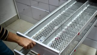 A worker of a pharmacy opens an empty drewer in Caracas on May 30, 2016. The shortage of medicines in Venezuela exceeds 85%, revealed the president of the farmaceutical federation of Venezuela, Freddy Ceballos. / AFP PHOTO / RONALDO SCHEMIDT