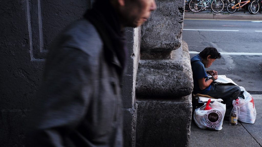 A woman with her belongings rests leaning on a wall as pedestrians walk past in New York on September 15, 2016.  / AFP PHOTO / Jewel SAMAD