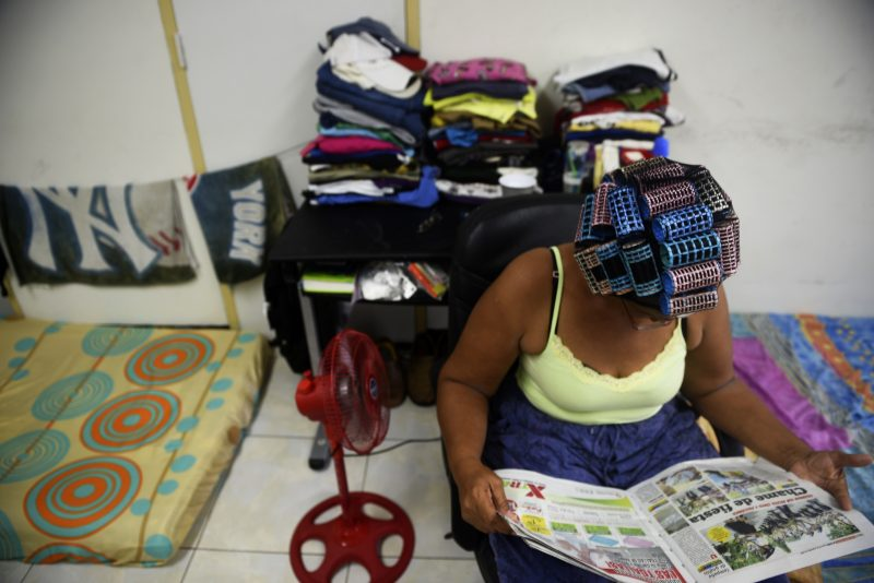 A Cuban migrant reads a newspaper in the Pastoral Social Caritas Panama shelter, on September 20, 2016 in Panama City.  Every month hundreds of Cubans cross on boats the border from Colombia to Puerto Obaldia, in Panama, on their way to the US. / AFP PHOTO / RODRIGO ARANGUA