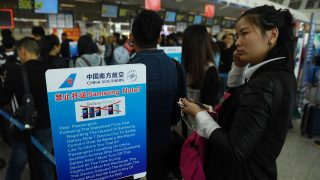 Passengers line up beside a safety warning about the Samsung Galaxy Note 7 smartphone at a checkin counter at the airport in Wuhan, in China's central Hubei province on October 2, 2016. Samsung says it will resume sales of new Galaxy Note 7 smartphones in South Korea this week, hoping to turn the page on the troubled device after an ongoing global recall prompted by battery explosions. / AFP PHOTO / GREG BAKER