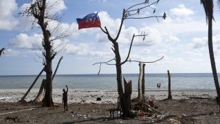 """A boy waves next to a national Haiti flag in a tree on a beach destroyed by Hurricane Matthew in Port Salut southwest of Port-au-Prince, on October 11, 2016.  Haiti faces a humanitarian crisis that requires a """"massive response"""" from the international community, the United Nations chief said Monday, with at least 1.4 million people needing emergency aid following last week's battering by Hurricane Matthew. The storm left at least 372 dead in the impoverished Caribbean nation, with the toll likely to rise sharply as rescue workers reach previously inaccessible areas. / AFP PHOTO / RODRIGO ARANGUA"""