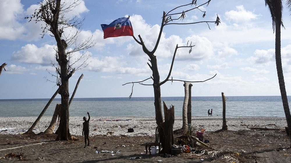 "A boy waves next to a national Haiti flag in a tree on a beach destroyed by Hurricane Matthew in Port Salut southwest of Port-au-Prince, on October 11, 2016.  Haiti faces a humanitarian crisis that requires a ""massive response"" from the international community, the United Nations chief said Monday, with at least 1.4 million people needing emergency aid following last week's battering by Hurricane Matthew. The storm left at least 372 dead in the impoverished Caribbean nation, with the toll likely to rise sharply as rescue workers reach previously inaccessible areas. / AFP PHOTO / RODRIGO ARANGUA"