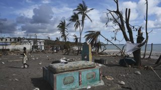 """A mattress is dried in the sun on a grave at a beach destroyed by Hurricane Matthew in Port Salut southwest of Port-au-Prince, on October 11, 2016.  Haiti faces a humanitarian crisis that requires a """"massive response"""" from the international community, the United Nations chief said Monday, with at least 1.4 million people needing emergency aid following last week's battering by Hurricane Matthew. The storm left at least 372 dead in the impoverished Caribbean nation, with the toll likely to rise sharply as rescue workers reach previously inaccessible areas. / AFP PHOTO / RODRIGO ARANGUA"""