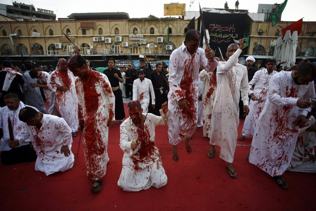 Iraqi Shiite Muslim men flagellate themselves on the tenth day of the mourning period of Muharram, which marks the day of Ashura, in the holy city of Najaf on October 12, 2016.    Ashura mourns the death of Imam Hussein, a grandson of the Prophet Mohammed, who was killed by armies of the Yazid near Karbala in 680 AD. / AFP PHOTO / Haidar HAMDANI