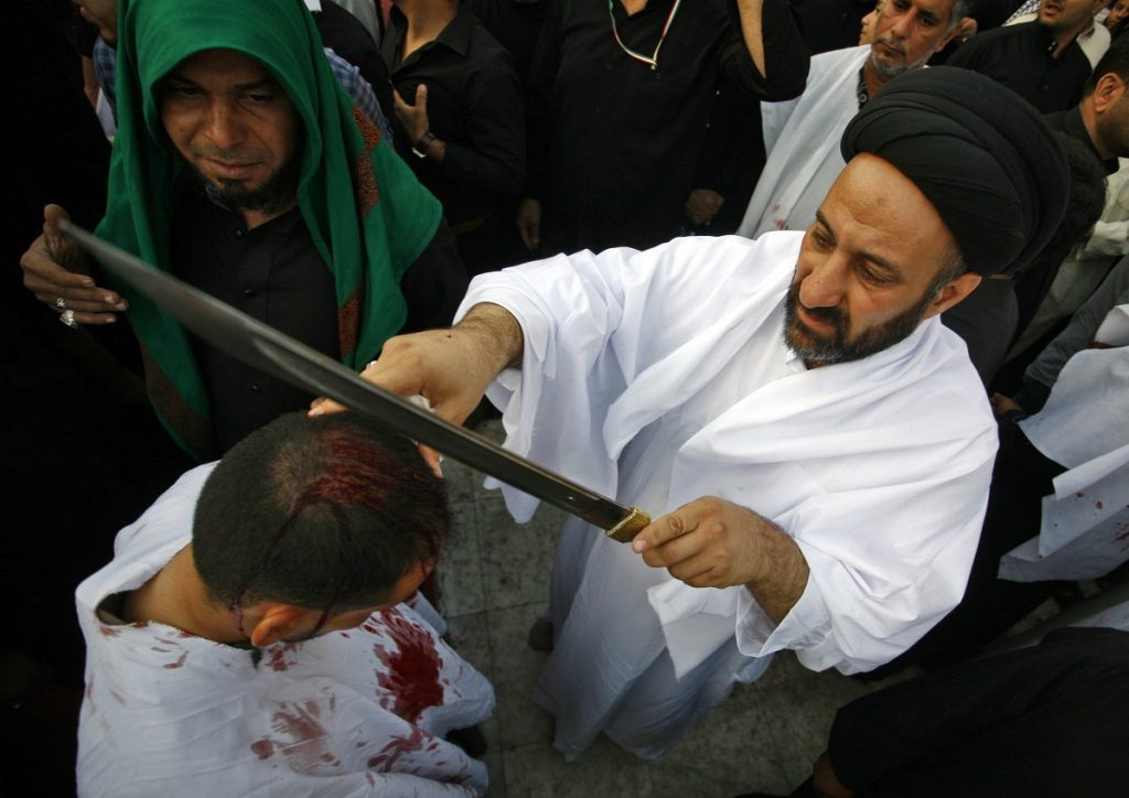 Iraqi Shiite Muslim boy is seen before being cut on the head, in ritual commemorating the death of Imam Hussein,Prophet Mohammed's grandson on the tenth day of the mourning period of Muharram, which marks the day of Ashura, in the holy city of Najaf on October 12, 2016.    Ashura mourns the death of Imam Hussein, a grandson of the Prophet Mohammed, who was killed by armies of the Yazid near Karbala in 680 AD. / AFP PHOTO / STR/HAIDAR HAMDANI