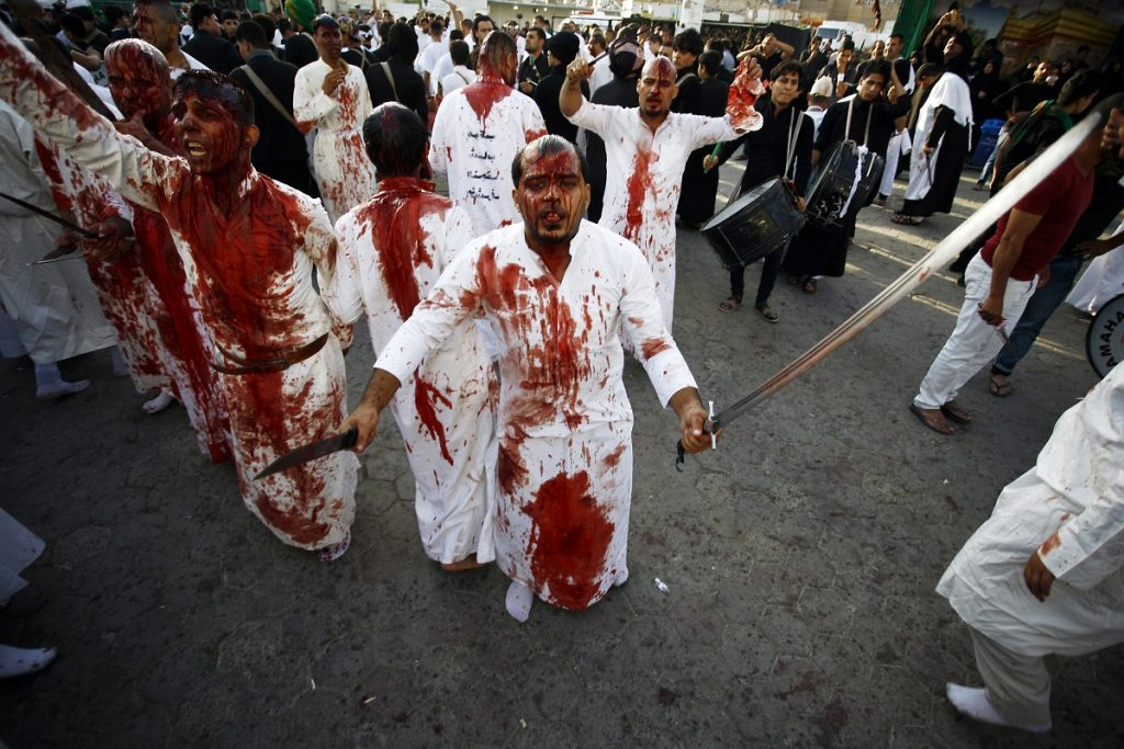 Iraqi Shiite Muslim men flagellate themselves on the tenth day of the mourning period of Muharram, which marks the day of Ashura, in the holy city of Najaf on October 12, 2016.    Ashura mourns the death of Imam Hussein, a grandson of the Prophet Mohammed, who was killed by armies of the Yazid near Karbala in 680 AD. / AFP PHOTO / STR/HAIDAR HAMDANI