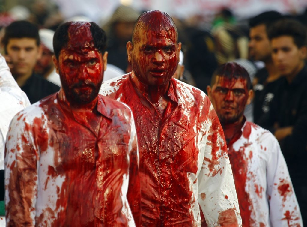 Iraqi Shiite Muslim men are seen after flagellating themselves on the tenth day of the mourning period of Muharram, which marks the day of Ashura, in the holy city of Najaf on October 12, 2016.    Ashura mourns the death of Imam Hussein, a grandson of the Prophet Mohammed, who was killed by armies of the Yazid near Karbala in 680 AD. / AFP PHOTO / Haidar HAMDANI