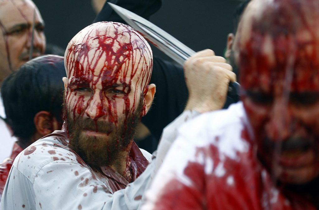 Iraqi Shiite Muslim men are seen after flagellating themselves on the tenth day of the mourning period of Muharram, which marks the day of Ashura, in the holy city of Najaf on October 12, 2016.    Ashura mourns the death of Imam Hussein, a grandson of the Prophet Mohammed, who was killed by armies of the Yazid near Karbala in 680 AD. / AFP PHOTO / STR/HAIDAR HAMDANI