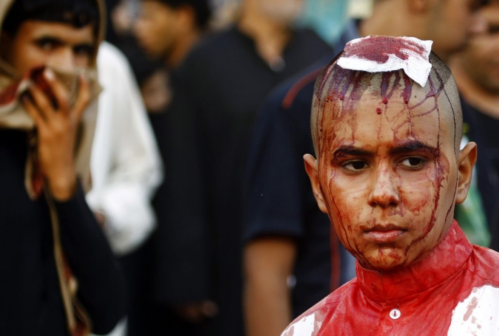 Iraqi Shiite Muslim boy is seen after being flagellated on the tenth day of the mourning period of Muharram, which marks the day of Ashura, in the holy city of Najaf on October 12, 2016.    Ashura mourns the death of Imam Hussein, a grandson of the Prophet Mohammed, who was killed by armies of the Yazid near Karbala in 680 AD. / AFP PHOTO / STR/HAIDAR HAMDANI