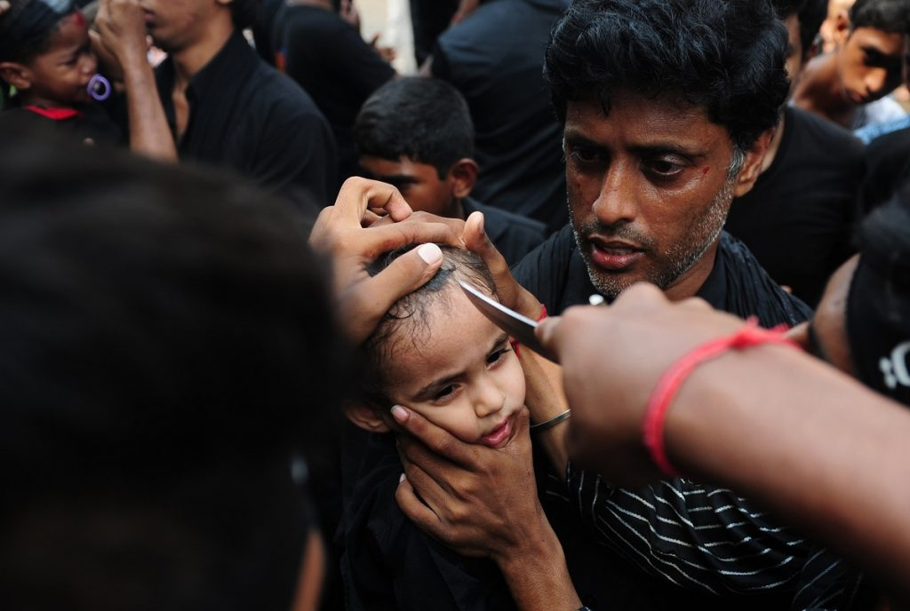 A young Indian Shia Muslim child is flagellated during the mourning procession on the tenth day of Muharram, which marks the day of Ashura, in Chennai on October 12, 2016. Ashura mourns the death of Imam Hussein, a grandson of the Prophet Mohammed, who was killed by armies of the Yazid near Karbala in 680 AD. / AFP PHOTO / ARUN SANKAR