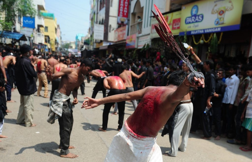 Indian Shia Muslim men self-flagellate during the mourning procession on the tenth day of Muharram, which marks the day of Ashura, in Chennai on October 12, 2016. Ashura mourns the death of Imam Hussein, a grandson of the Prophet Mohammed, who was killed by armies of the Yazid near Karbala in 680 AD. / AFP PHOTO / ARUN SANKAR