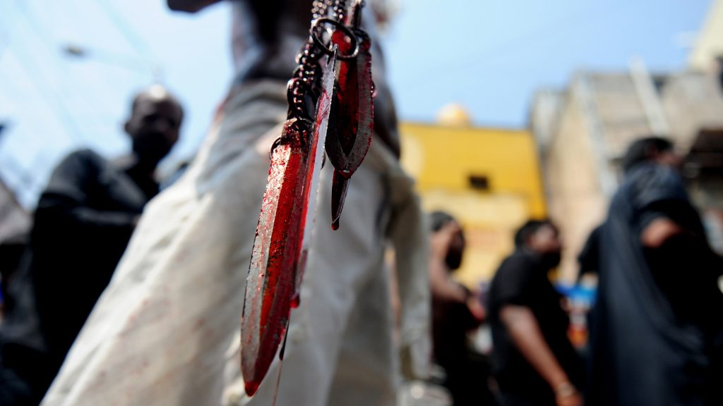 An Indian Shia Muslim man holds blood-stained blades as he self-flagellates during the mourning procession on the tenth day of Muharram, which marks the day of Ashura, in Chennai on October 12, 2016. Ashura mourns the death of Imam Hussein, a grandson of the Prophet Mohammed, who was killed by armies of the Yazid near Karbala in 680 AD. / AFP PHOTO / ARUN SANKAR