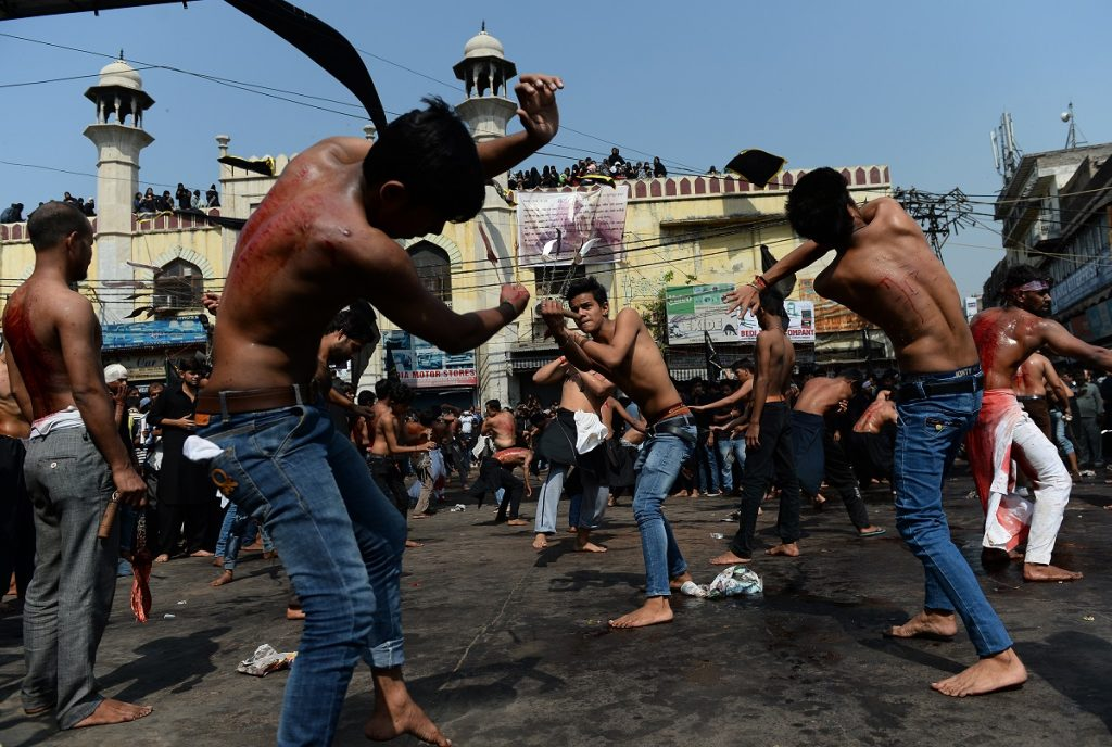 Indian Shia Muslim men flagellate themselves during the mourning procession on the tenth day of Muharram, which marks the day of Ashura, in the old quarters of New Delhi on October 12, 2016. Ashura mourns the death of Imam Hussein, a grandson of the Prophet Mohammed, who was killed by armies of the Yazid near Karbala in 680 AD. / AFP PHOTO / SAJJAD HUSSAIN