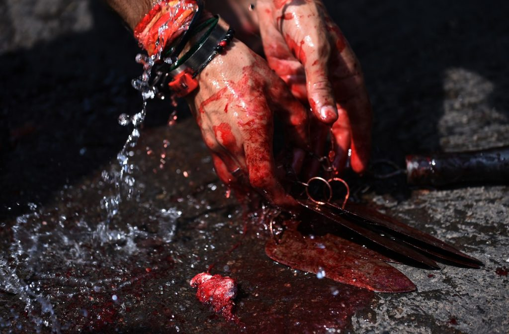 An Indian Shia Muslim men sets down blades used to flagellate himself during the mourning procession on the tenth day of Muharram, which marks the day of Ashura, in the old quarters of New Delhi on October 12, 2016. Ashura mourns the death of Imam Hussein, a grandson of the Prophet Mohammed, who was killed by armies of the Yazid near Karbala in 680 AD. / AFP PHOTO / SAJJAD HUSSAIN