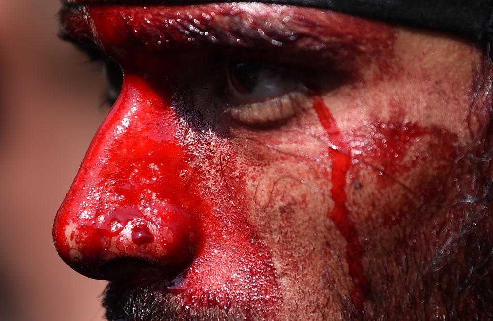 An Indian Shia Muslim men face is covered with blood after he flagellated himself during the mourning procession on the tenth day of Muharram, which marks the day of Ashura, in the old quarters of New Delhi on October 12, 2016. Ashura mourns the death of Imam Hussein, a grandson of the Prophet Mohammed, who was killed by armies of the Yazid near Karbala in 680 AD. / AFP PHOTO / SAJJAD HUSSAIN