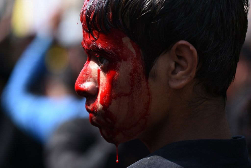An Indian Shia Muslim youth's face covered with blood after he flagellated himself during the mourning procession on the tenth day of Muharram, which marks the day of Ashura, in the old quarters of New Delhi on October 12, 2016. Ashura mourns the death of Imam Hussein, a grandson of the Prophet Mohammed, who was killed by armies of the Yazid near Karbala in 680 AD. / AFP PHOTO / SAJJAD HUSSAIN