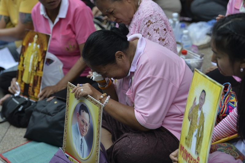 Supporters of Thailand's King Bhumibol Adulyadej react as they pray at Siriraj Hospital, where the king is being treated, in Bangkok on October 13, 2016. Well-wishers kept up their vigil outside a Bangkok hospital on October 13, offering prayers for ailing King Bhumibol Adulyadej as Thailand faces the prospect of losing its figure of unity in a deeply polarized nation. / AFP PHOTO / MUNIR UZ ZAMAN