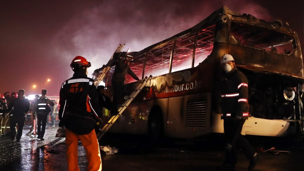 Fire and rescue services attend the scene of a bus accident near Ulsan, on South Korea's south-eastern coast on October 14, 2016. At least 10 people were killed and seven others seriously injured as their tour bus caught fire on a highway near South Korea's southeastern city of Ulsan, police said. The bus was carrying 20 people late October 13 night when one of the front tires exploded, causing it to crash into a concrete guardrail and catch fire, South Korea's Yonhap news agency reported citing a witness of the fatal accident.  / AFP PHOTO / YONHAP / Yonhap /  - South Korea OUT / REPUBLIC OF KOREA OUT  NO ARCHIVES  RESTRICTED TO SUBSCRIPTION USE