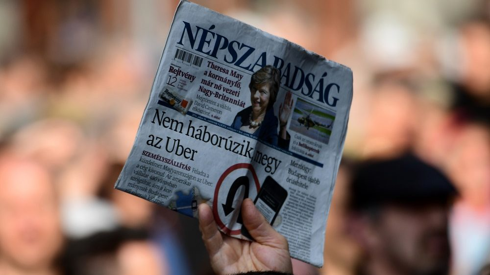 A person holds a copy of Nepszabadsag daily during a protest by journalists of Hungary's biggest opposition newspaper Nepszabadsag and their supporters in Budapest on October 16, 2016.   The newspaper suspended its activities, heightening concerns about media plurality under right-wing Prime Minister Viktor Orban. / AFP PHOTO / ATTILA KISBENEDEK