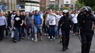Legia Warsaw football fans are escorted by Spanish poilce into the stadium to take their seats ahead of the UEFA Champions League football match Real Madrid CF vs Legia  Legia Warszawa at the Santiago Bernabeu stadium in Madrid on October 18, 2016. Three Polish football fans were arrested  today after they attacked waitresses in a bar in the La Latina district of Madrid, stealing the mobile phone of one woman and attempting to rob cash from the till, a police spokesperson confirmed to AFP.   / AFP PHOTO / PIERRE-PHILIPPE MARCOU