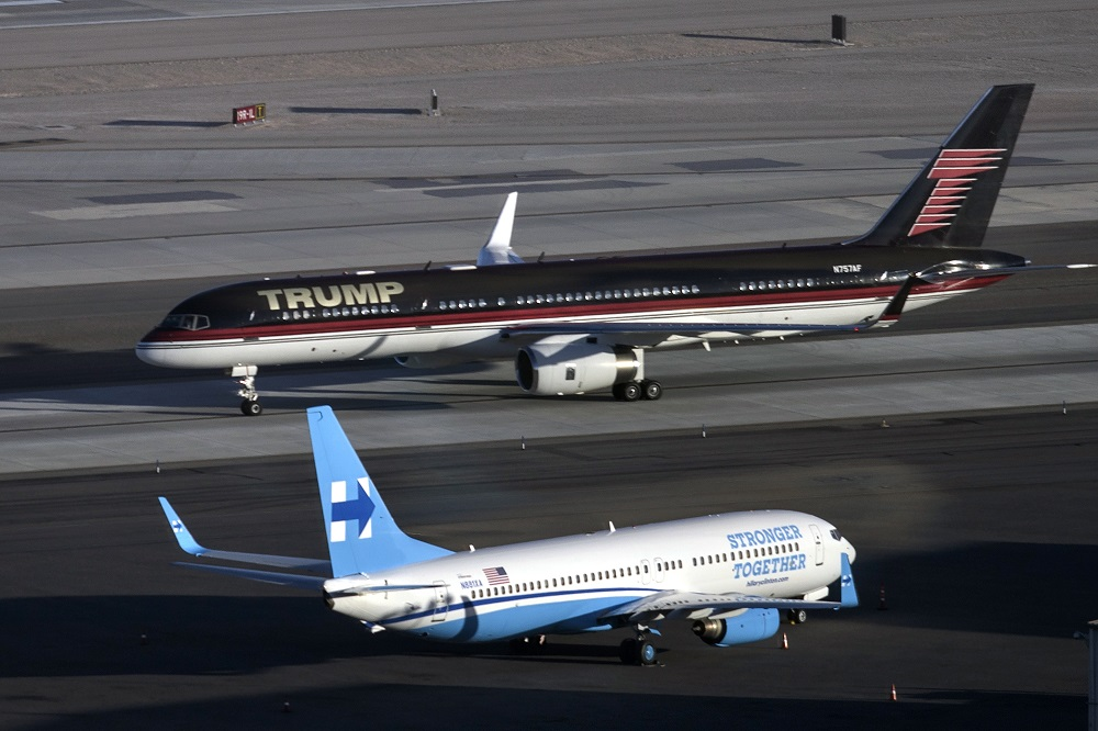 Republican presidential nominee Donald Trump's plane (TOP) passes Democratic presidential nominee Hillary Clinton's campaign plane at McCarran International Airport on October 18, 2016 in Las Vegas, Nevada, on the eve of the two candidates' third and final US presidential debate. / AFP PHOTO / Brendan Smialowski