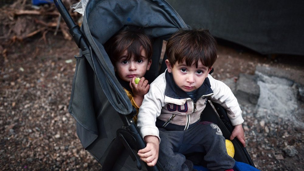 Twin brothers look on from their pram inside the Ritsona refugee camp, north of Athens on October 21, 2016. The camp hosts some 500 refugees, mostly Syrian and Syrian-Kurd families living in tents and waiting to move to container houses. More than 60.000 refuges are stranded in Greece since the closure of the borders. / AFP PHOTO / LOUISA GOULIAMAKI