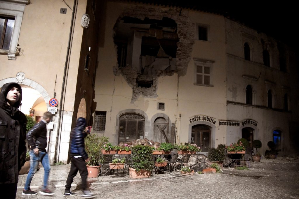 """People walk past a destroyed building in the village of Visso, central Italy, after earthquakes on October 26, 2016. Twin earthquakes rocked central Italy on October 26, 2016 -- the second registering at a magnitude of 6.0 -- in the same region struck in August by a devastating tremor that killed nearly 300 people. The quakes were felt in the capital Rome, sending residents running out of their houses and into the streets. The second was felt as far away as Venice in the far north, and Naples, south of the capital. / AFP PHOTO / TIZIANA FABI / """"The erroneous mention[s] appearing in the metadata of this photo by TIZIANA FABI has been modified in AFP systems in the following manner: [Visso] instead of [Borgo Sant'Antonio]. Please immediately remove the erroneous mention[s] from all your online services and delete it (them) from your servers. If you have been authorized by AFP to distribute it (them) to third parties, please ensure that the same actions are carried out by them. Failure to promptly comply with these instructions will entail liability on your part for any continued or post notification usage. Therefore we thank you very much for all your attention and prompt action. We are sorry for the inconvenience this notification may cause and remain at your disposal for any further information you may require."""""""
